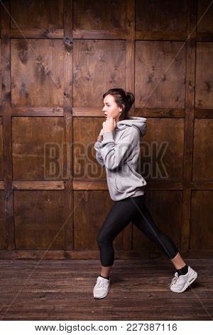 Brunette Adult In Grey Hoodie Doing Aerobics. Sport Concept.