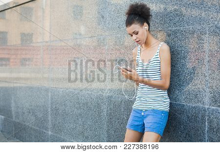 Tired Young Woman Runner Is Having Break, Standing Near Grey Wall After Jogging In City Center, Copy