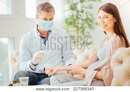 Best Specialists. Qualified Pleasant Calm Medic In A Gauze Mask Sitting In The Bright Room Near A Wo