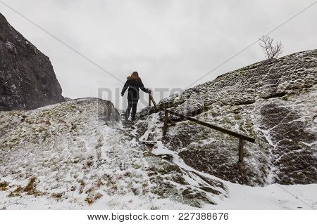 Woman Walking Alone, Climbing A Mountain In Snowy Weather. Viewpoint Jossingfjord, Rogaland In Norwa