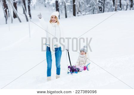 Happy Daughter And Mother Sledging Together In Winter Park