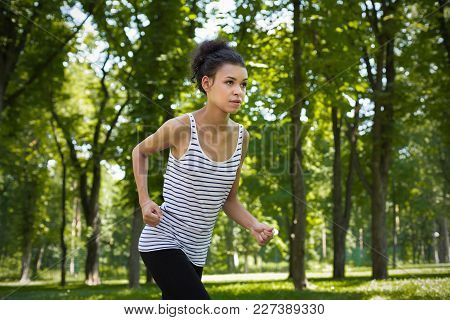 Young Sporty African-american Woman Running In Green Park During Morning Workout, Copy Space