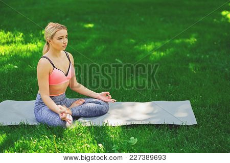 Young Woman Outdoors, Meditation Exercises. Girl Does Lotus Pose For Relaxation. Wellness, Calmness,