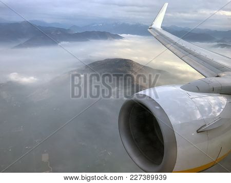 Aerial View On Fogy Mountains From Airplane