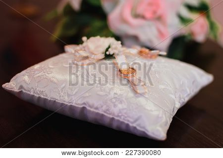 Gold Wedding Rings On White Pillow Decorated