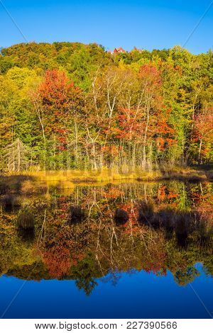 Magnificent resort in French Canada, Mont Tremblant. Multicolored foliage of autumn forests is reflected in ponds is smooth like a mirror. Concept of ecological and automobile tourism
