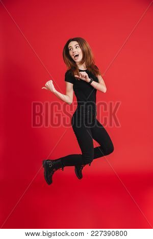 Full length of an excited casual girl jumping and pointing fingers away isolated over pink background