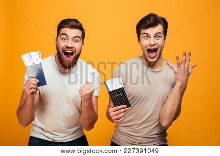 Portrait of a two excited young men holding passports with flying tickets and celebrating isolated over yellow background