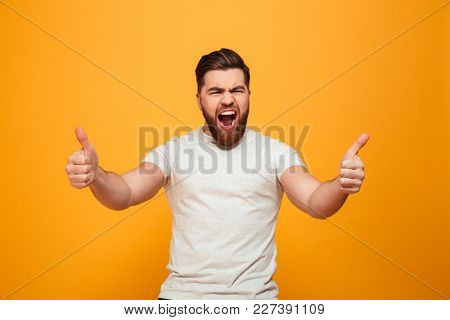 Portrait of an excited bearded man showing thumbs up isolated over yellow background