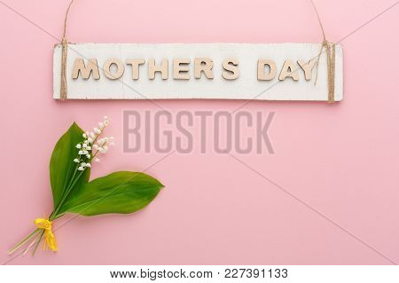 Mothers Day Background. Rustic Wooden Plank With Letters Hanging On Twine And May-lilies At Tender P