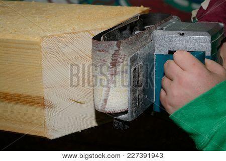 Wooden Beam Is Smoothed By Craftsmen With Belt Sander
