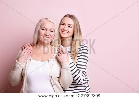 Young daughter and mother on color background