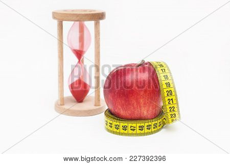 Measuring Metter With Red Apples And Sand Glass Clock, Isolated On White Background With Copy Space.