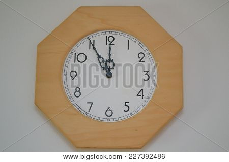 Wooden Wall Clock Shows Five To Twelve As The Time