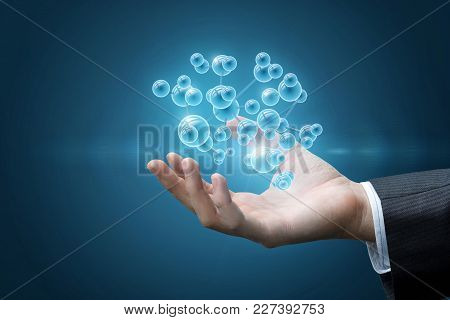 Hand Shows The Molecules On A Blue Background.