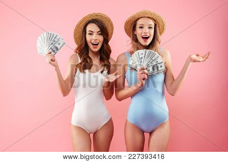 Two rich girls on vacation in summer clothing rejoicing and holding fans of money dollar currency in hands isolated over pink background