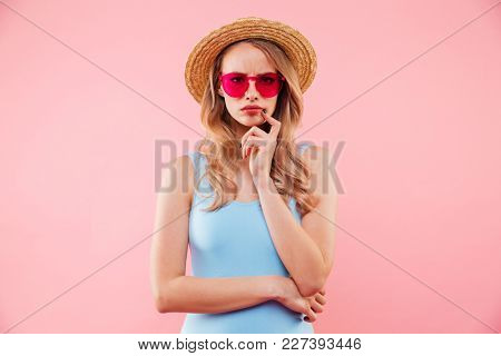 Young serious girl in sunglasses wearing colorful one-piece swimsuit and straw hat posing on camera with meaningful look isolated over pink background