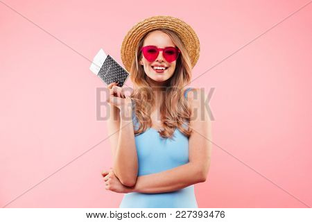 Beautiful woman in sunglasses wearing one-piece swimsuit and straw hat smiling while holding passport and tickets isolated over pink background