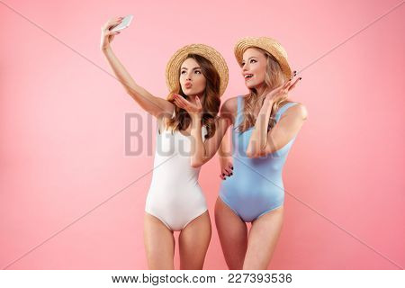Two brunette and blonde women in one-piece colorful swimsuits and straw hats smiling and taking selfie on cell phone isolated over pink background