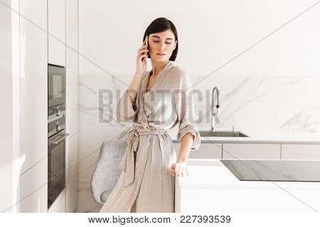 Single woman with short dark hair wearing sexual robe posing in kitchen and speaking on mobile phone