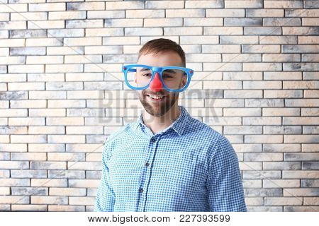 Young man in funny disguise posing on brick wall background. April fool's day celebration