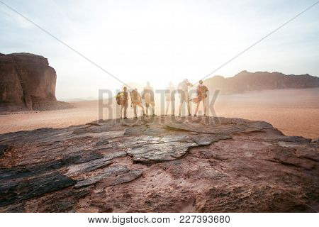 Tourist Friends On A Top Of Mountains In A Desert. Sunset View. Nature. Tourist People Enjoy A Momen
