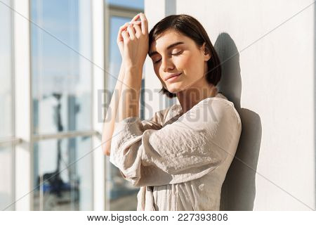 Portrait of elegant woman with short dark hair in housecoat standing sunlit near window in flat and covering face in sunny morning