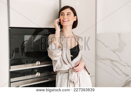 Photo of smiling woman with short dark hair wearing beautiful robe posing in kitchen and speaking on smartphone