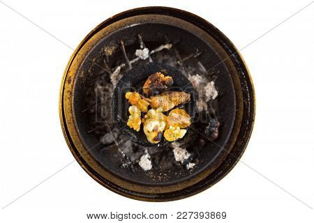 Top view of aromatic yellow resin gum from Sudanese Frankincense tree on burning Arabian charcoal  in brass burner, isolated on white