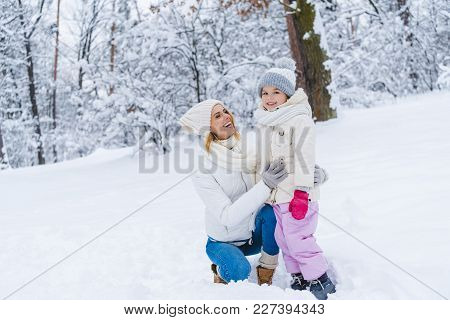 Happy Mother And Daughter Hugging In Winter Park