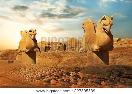 Sculptures Of Griffins In Ancient Persepolis Against The Backdrop Of The Rising Sun. Iran. Ancient P