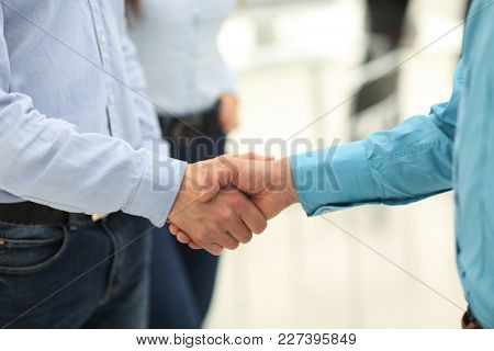 Businessman and a co-worker shaking hands during a meeting.