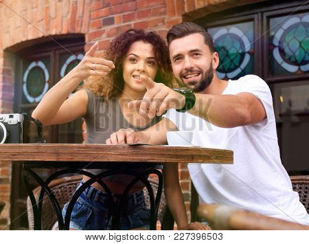 Happy couple drinking coffee in outdoors cafe on summer vacation