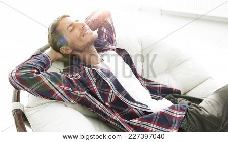 modern guy is resting sitting in a large comfortable chair. side