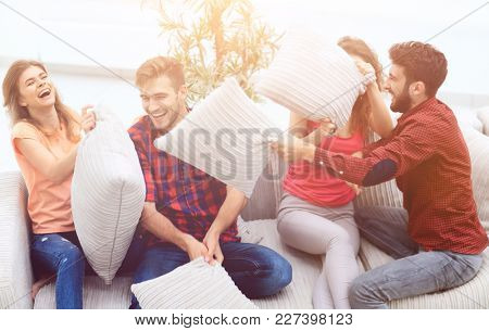 group of friends playing pillow fight, sitting on the couch