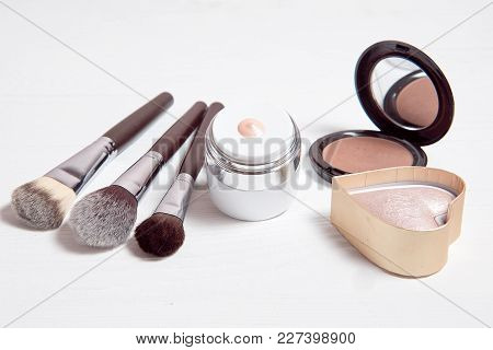 Professional Makeup Tools On White Wooden Background. Highlighter, Sculptor, Powder For Sculpting, K