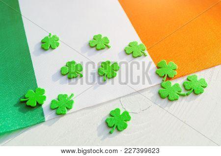 St Patrick's Day Festive Background. Green Quatrefoils Above The Irish National Flag