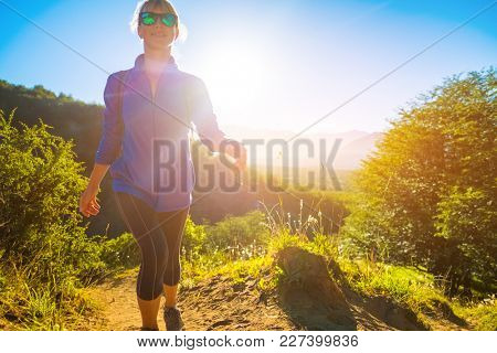 Woman hiker walks on the trail during sunrise