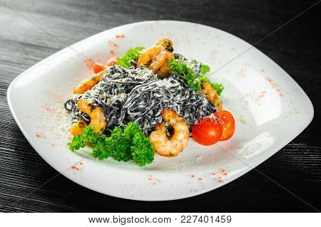 Black Pasta With Shrimp And Seafood. Black Wood Background