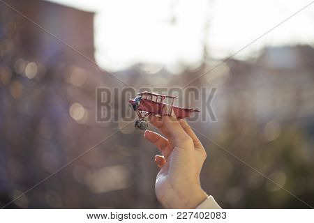 Hand Holding A Red Toy Plane. Holiday Concept. Hands Of Woman Holding A Red Toy Plane And Have Dream