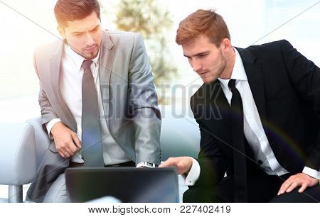 two colleagues working on a laptop sitting in the lobby of the o