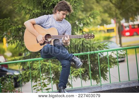 Handsome Young Man Playing Guitar Outdoors, Enjoying His Hobby