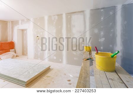 Putty Knife, Yellow Buckets With Glue And Glue Rollers On The Wooden Board In Room  Is Under Constru