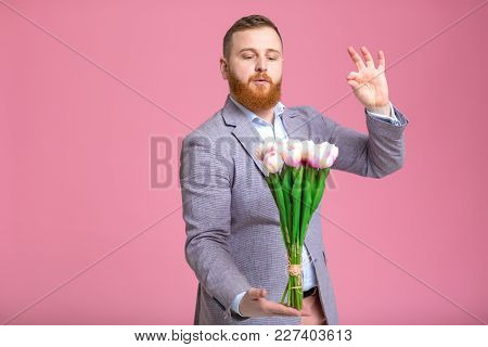 Handsome Bearded Man Holding Bouquet Of Tulips In Hand On Pink Background. Womens Day.