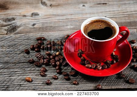 Cup Of Fresh Coffee With Coffee Beans On Wooden Table