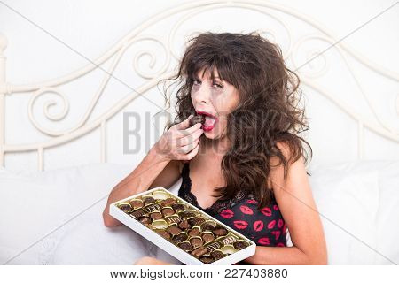 Upset Mature Woman Crying And Eating Chocolates In Her Bedroom