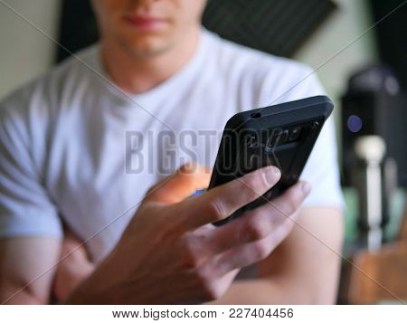 Man Holding Smartphone / Cell Phone In Hand With Blank Screen.