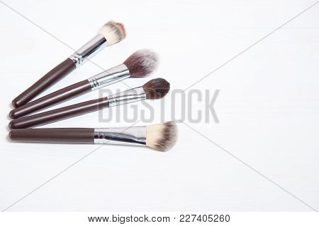 Professional Makeup Brushes On White Wooden Background.