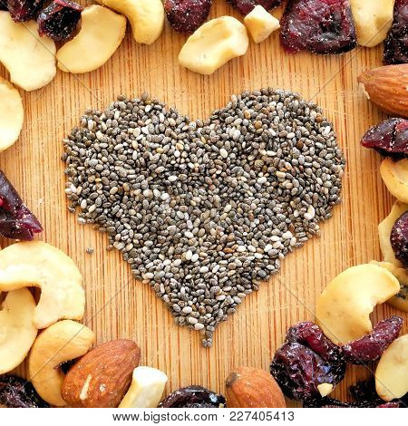 Mixed Fruits,nuts, And Chia Seeds Heart On Wood Grain Cutting Board, Arranged In Square For Social M