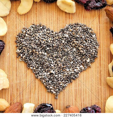 Mixed Fruits,nuts, And Chia Seed Heart On Wood Grain Cutting Board, Arranged In Square For Social Me